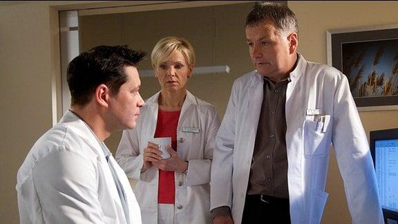 Dr. Philipp Brentanos (Thomas Koch, li.) bittet Dr. Kathrin Globisch (Andrea Kathrin Loewig, mi.) und Dr. Roland Heilmann (Thomas Rühmann, re.) um Rat.