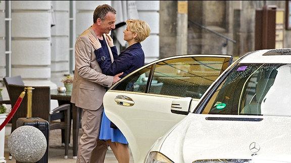 Kathrin Globisch (Andrea Kathrin Loewig) ist gerade mit Alexander Weber (Heio von Stetten) aus Paris zurückgekehrt und umarmt ihn am Auto.