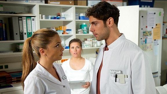 Schwester Julia (Sarah Tkotsch, mi.) hat Gefühle für Dr. Niklas Ahrend (Roy Peter Link, re.). Als sie erfährt, dass Niklas mal in die schöne Schwester Arzu (Arzu Bazman) verliebt war, glaubt sie nicht daran, dass er jemals Interesse an ihr haben könnte.