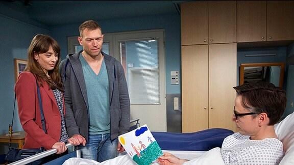 Patient liegt im Krankenbett, Mann und Frau stehen davor.