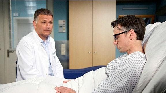 Patient liegt im Krankenbett, Arzt sitzt daneben.