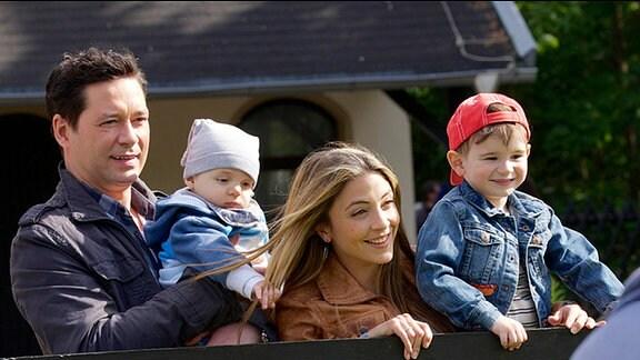 Mann und Frau halten zwei kleine Kinder.