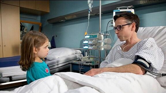 Patien liegt im Krankenbett, kleines Mädchen steht davor.