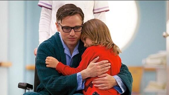 Mann im Rollstuhl hält kleines Mädchen im Arm