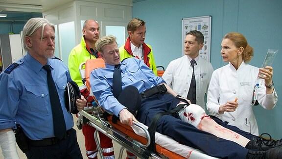 Bei einem Einsatz wurden Polizeioberwachtmeister Klaus Ramme und Polizeianwärter Henry Wegmann von betrunkenen Schlägern verletzt. In der Sachsenklinik werden sie von den Notärzten an Dr. Kaminski und Oberschwester Ingrid übergeben.