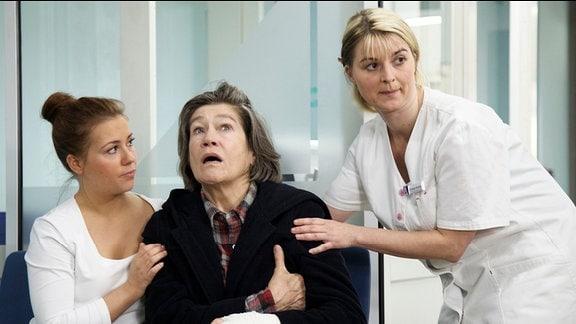 Regina Horner (Tina Engel, mi.) hat trotz dem hohem Risiko eines Herzinfarktes auf eigene Verantwortung die Klinik verlassen. Nun hat sie tatsächlich Schmerzen im Brustbereich. Schwester Julia Weiߟ (Sarah Tkotsch, li.) und ihre Kollegin (Komparsin, re.) verständigen sofort einen Arzt.