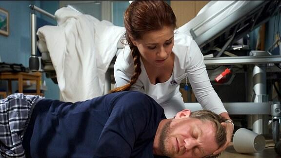 Schwester Julia findet Marc Dahlmann ohnmächtig vor seinem Bett liegen.