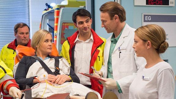Nicole Lamprecht (Judith Hoersch, mi.) wird von den Notärzten (Komparsen) nach einer Ohnmacht mit Atemnot in die Sachsenklinik eingeliefert.