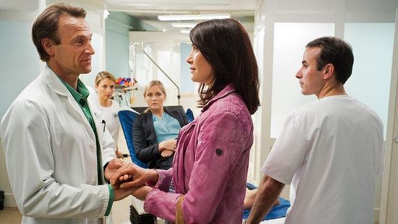 Antonia Bach (Claudia Mehnert, 2.v.re.) und  Dr. Martin Stein (Bernhard Bettermann, li.) halten Händchen. Im Hintergrund:  Nicole Lamprecht (Judith Hoersch, mi.) auf einer Krankenliege.