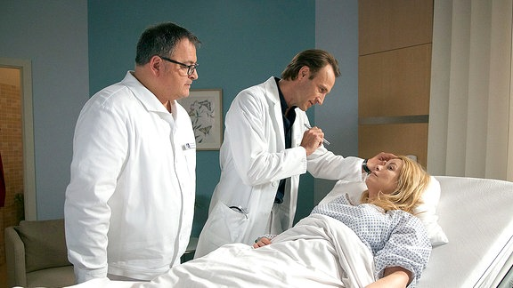 Sarah Marquardt liegt im Bett. Sie wird von Pfleger Hans-Peter Brenner und Dr. Martin Stein untersucht.