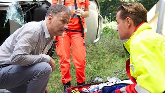 Nach dem Unfall, in den er selbst verwickelt war, eilt Dr. Heilmann (Thomas Rühmann, links) sofort herbei, um Hilfe zu leisten.