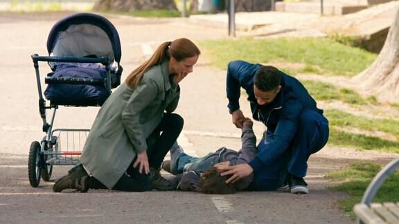 Ein Mann liegt auf einem Parkweg. Zwei Passanten helfen ihm.