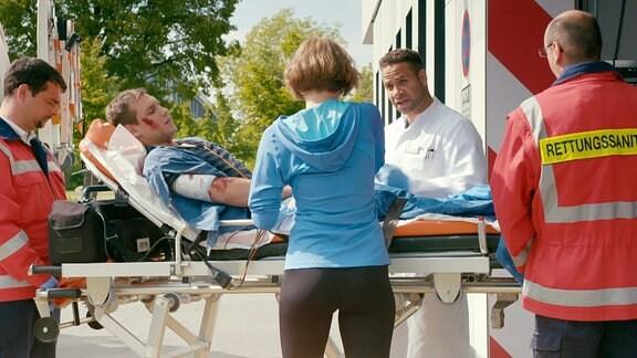 Ein Mann mit Verletzungen wird von einem Rettungsteam versorgt.