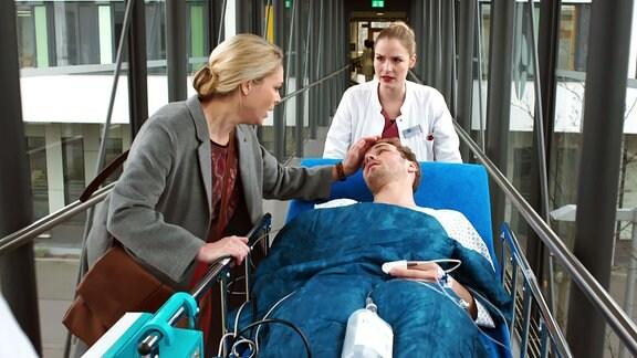 Eine Frau streicht einem Mann auf einer Krankenliege über das Gesicht. Dahinter ein Ärztin.