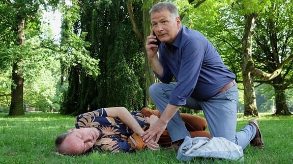 Roland Heilmann (Thomas Rühmann, re.) hockt neben dem bewusstlosen Achim Kreutzer, fühlt den Puls und telefoniert.