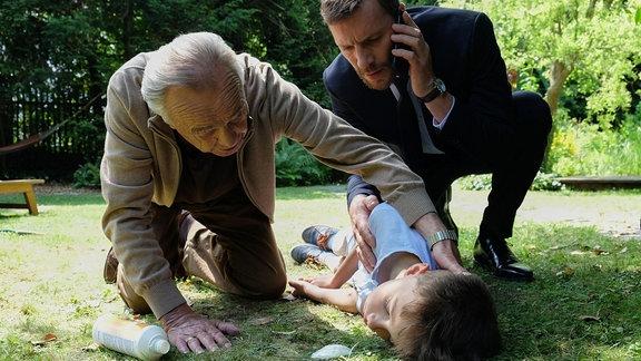 Während Professor Simoni (Dieter Bellmann, li.) mit Björn Gerdes (Knut Berger, re.), dem Vater des kleinen Robin (Alexander und Julian Hägele, unten), redet, ist dieser kurz unbeobachtet und trinkt einen Schluck aus einer Flasche. Doch es war Grillreiniger und Robin bricht röchelnd zusammen.