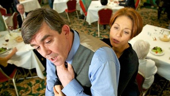 """Udo von Wackerstein (Dirk Schoedon) hat sich verschluckt und droht zu ersticken; Pia Heilmann (Hendrikje Fitz) setzt den in ihrer Ausbildung gelernten """"Heimlich-Handgriff"""" ein und rettet ihm so das Leben"""