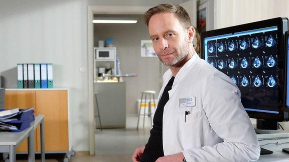 Arzt lehnt lässig an einem Computertisch