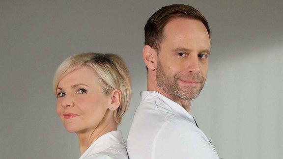 Zwei Ärzte Rücken an Rücken mit verschränkten Armen blicken in die Kamera.