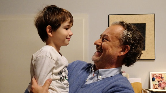 Kinderdarsteller Leo wird von Schauspieler  Rolf Kanis auf den Arm genommen.