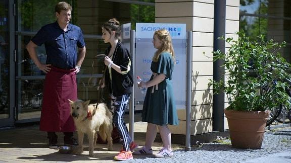 Ein Mann und zwei Frauen mit einem Hund vor der Sachsenklinik