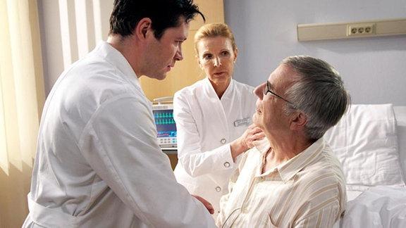 Im Gegensatz zu Prof. Simoni, vermutet Dr. Philipp Brentano (Thomas Koch, li.) eine harmlosere neurologische Ursache für Waldners Zustand, als einen Schlaganfall. Doch plötzlich ruft Oberschwester Ingrid (Jutta Kammann, mi.) aus Waldners Patientenzimmer um Hilfe. Nun hat Anton Waldner (Hubert Mulzer, re.) auch im Bein Ausfallerscheinungen. Dies widerlegt Brentanos These und veranlasst Simoni dazu, an der Sorgfalt des jungen Arztes zu zweifeln. Brentano steht nach seiner Aufputschmittelsucht immer noch unter strenger Beobachtung seiner Kollegen.