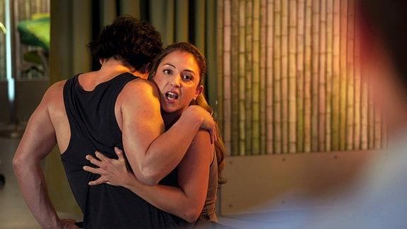 Eine Frau mit weit geöffnetem Mund umarmt einen Mann
