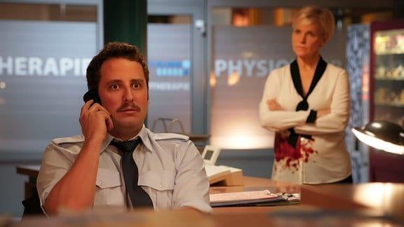 Ein Mann telefoniert, im Hintergrund steht eine Frau.