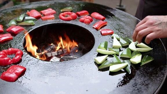 Paprika und Zucchini auf einem Grill im Freien.