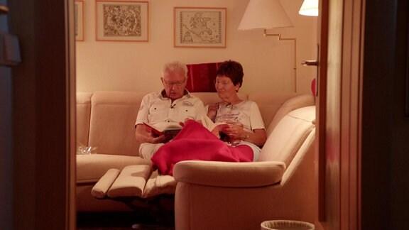 Älteres Pärchen kuschelt unter einer Decke auf einer Couch