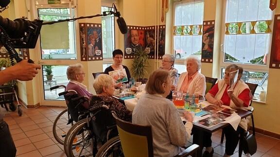 Gruppe von alten Menschen sitzt zusammen an einem Tisch und wird dabie gefilmt