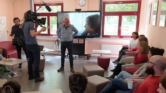 Dreharbeiten von Menschen, die auf Sesseln in einem Kreis sitzen, in der Mitte steht ein Mann vor einem großen Fernseher