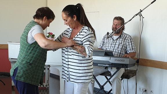 Pflegerin tanzt mit Frau, im Vordergrund steht ein Rollstuhl, im Hintergrund sitzt ein Mann am Keyboard