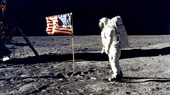 Astronaut Edwin 'Buzz' Aldrin steht neben einer US-Flagge auf der Mondoberfläche.