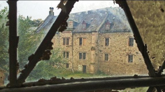 Blick durch ein Fenster auf einen Flügel von Schloss Reinhardsbrunn