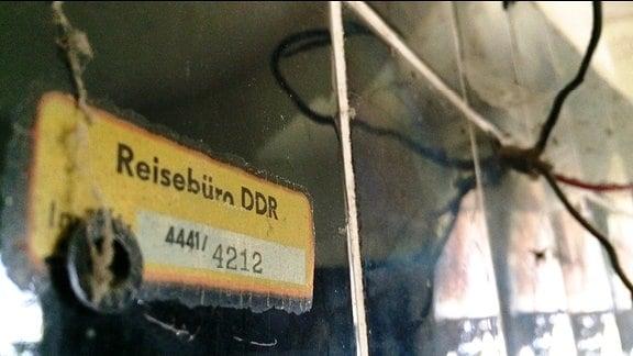 """Ein gelbes Schild mit der Aufschrift """"Reisebüro DDR"""""""