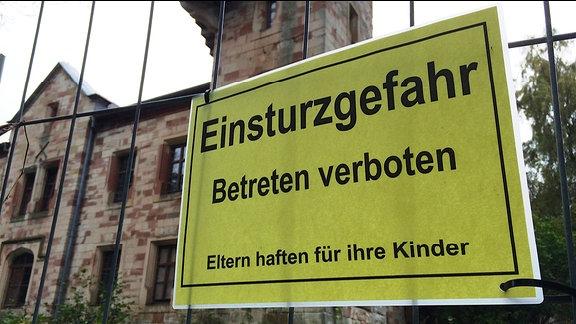"""Ein Schild mit der Aufschrift """"Einsturzgefahr Betreten verboten"""" an einem Bauzaun"""