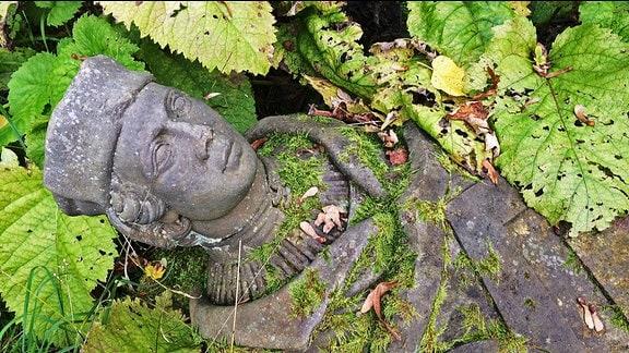 Die Steinfigur eines Mannes liegt zwischen Pflanzen auf dem Boden