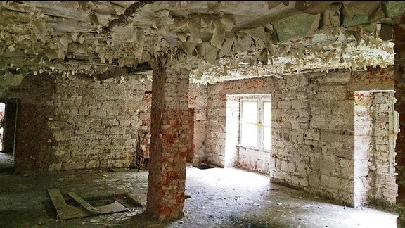 Farbe blättert von der Decke eines unverputzten Raumes