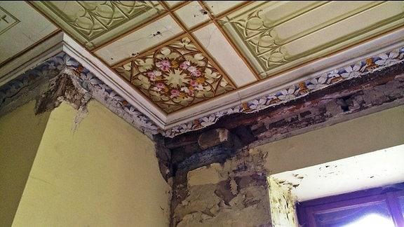 Die Decke in der Ecke eines Zimmers zeigt Schäden