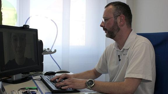 Arzt arbeitet an einem Computer.