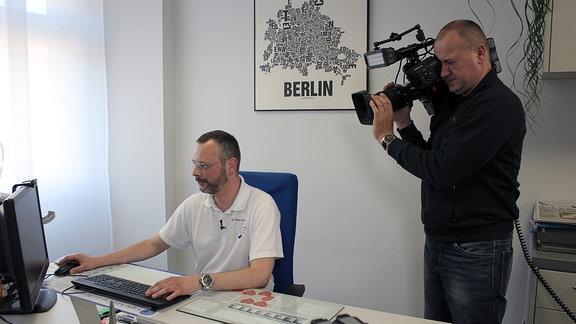 Kameramann filmt einen Arzt, der am Computer arbeitet.