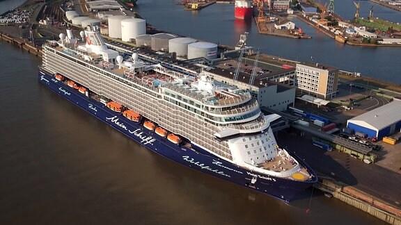 Ein weiß-blau lackiertes Kreuzfahrtschiff liegt in einem Hafen
