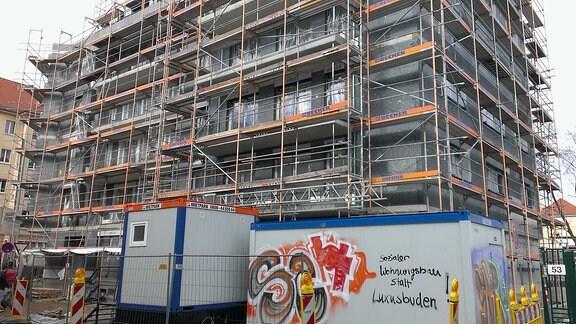 Wohnhaus mit Baugerüst, davor steht ein Baucontainer mit der Aufschrift sozialer Wohnungsbau statt Luxusbuden