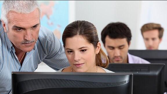 Eine Frau Arbeitet am PC und wird von einem Mann angewiesen.