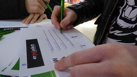 Hände füllen mit Kugelschreiber Umfragezettel aus