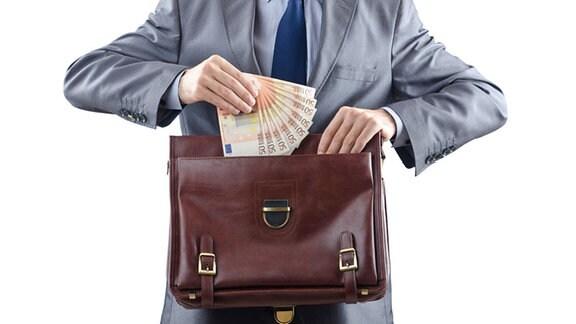 Mann hält gefächerte Euro-Scheine an Aktentasche