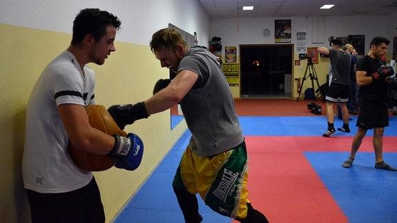 Mehrere Männer beim Boxtraining in einer Halle