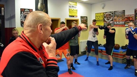 Ein Trainer zeigt beim Boxtraining einen Schlag