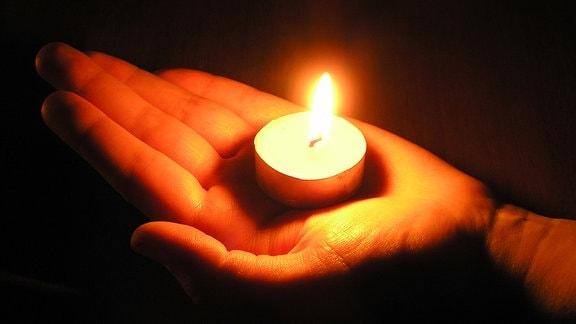 Brennende Kerze in einer Hand.